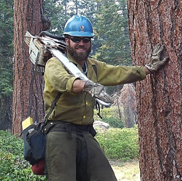 Photo of Arrowhead Hotshot Daniel Holmes - 2004, standing in his fire gear with chainsaw over right shoulder, and left hand leaning against a large pine tree.