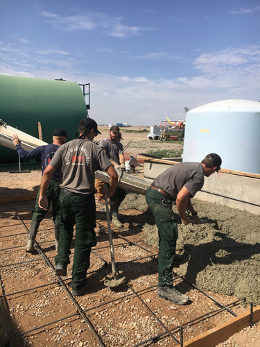 a crew of five men work at pouring concrete at an airtanker base.