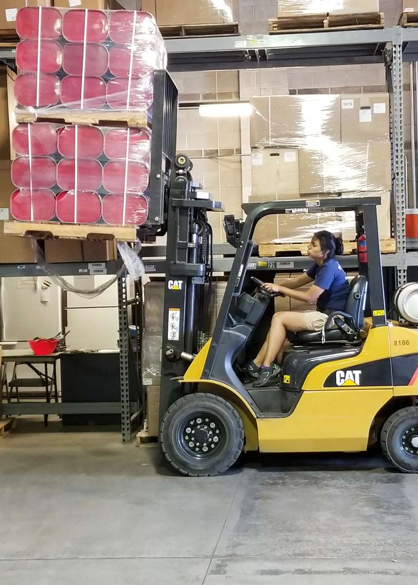 Forklift driver moving a pallet of supplies.
