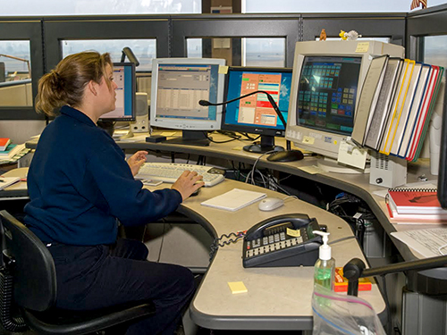 Female wildland fire dispatcher sits at a bank of computers reading the screens. Decorative.