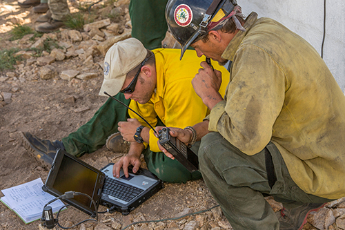 A fire fighter squats next to a division supervisor who is sitting on the ground reviewing data on a laptop sitting in front of him. Decorative.