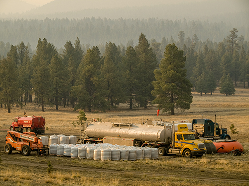 A chemical retardant mixing area in an open field on a fire assignment. Several trucks parked with bags of chemicals lined up and mixing tanks in background.
