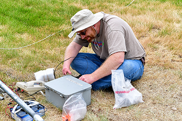 Fire weather training specialists sits cross legged on ground inspecting a RAWS weather station box.