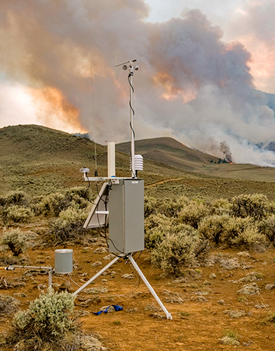 A RAWS weather station stands in sagebrush with active wildland fire in background. Decorative.