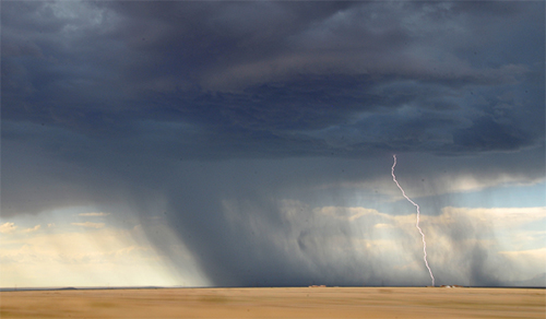 Heavy clouds and rainfall with a bolt of lightning striking dry grass plains. Decorative