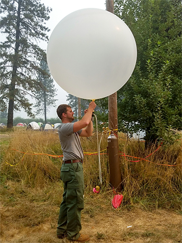 Fire weather specialist holding weather balloon ready to launch. Decorative.