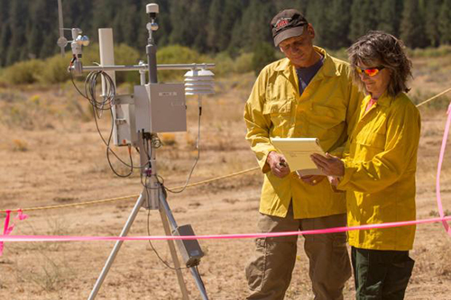 Two fire weather specialist standing in open area in front of a RAWS weather station reading documents. Decorative.