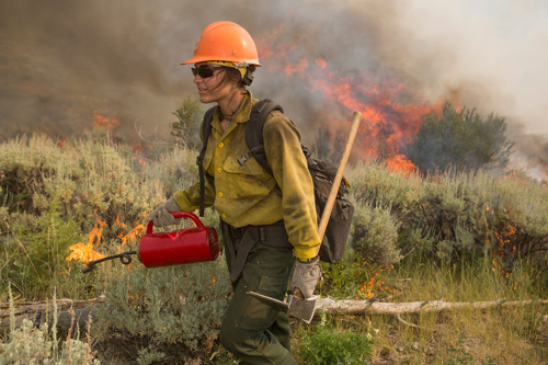 photo of firefighter walking with a drip torch