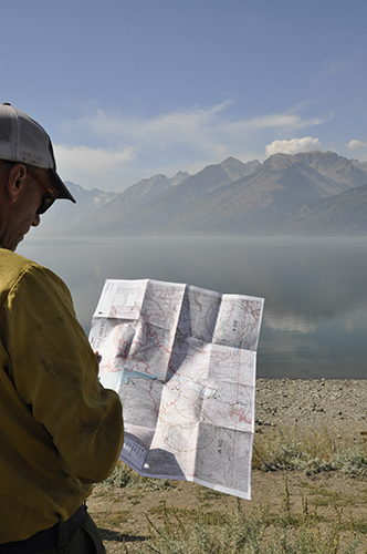 Photo of wildland firefighter reviewing a map in the field. Decorative.