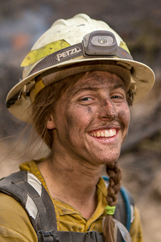 Decorative. A female wildland firefighter smiles at the camera, her face smudged with ashes and dirt.