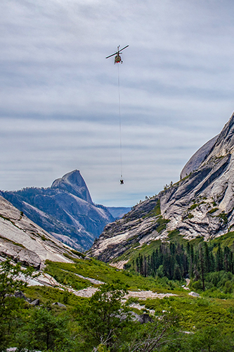 photo of a helicopter short haul operation transporting cargo on a long line through steep terrain.. Decorative.