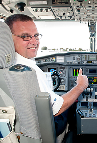Airtanker pilot looks back from cockpit with thumbs up gesture. Decorative.