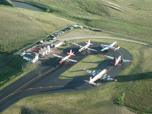 Aerial view of an airtanker base with five large planes on tarmac. Decorative