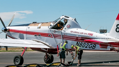 Two tanker base ground crew refuel a single engine airtanker. Decorative