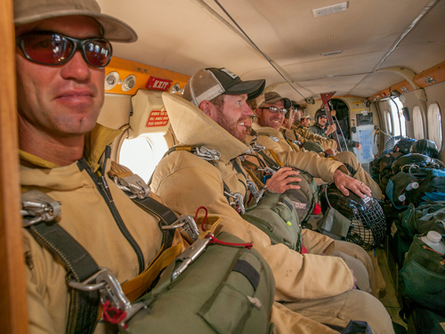 A group of wildland smokejumpers seated in a close-quarters jump plane. Decorative.