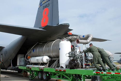 Three military personnel loading retardant carrier apparatus onto airtanker. Decorative