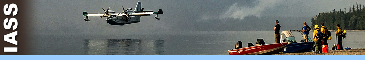 IASS header graphic. Photo of a water scooper plane landing on a lake with four people standing next to a boat on shore watch. Decorative.