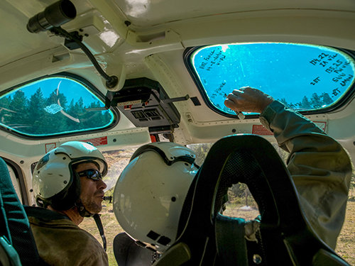 Two helicopter pilots in helicopter. Pilot on right is writing data on upper window. Decorative