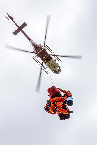 Helicopter hovers overhead while lifting a basket and two helicopter crew on hoist line. Decorative.