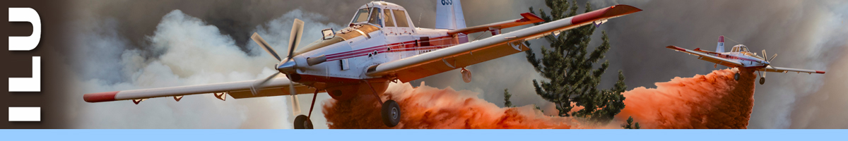 Two single engine airtankers dropping retardant over trees in heavy smoke. Decorative.