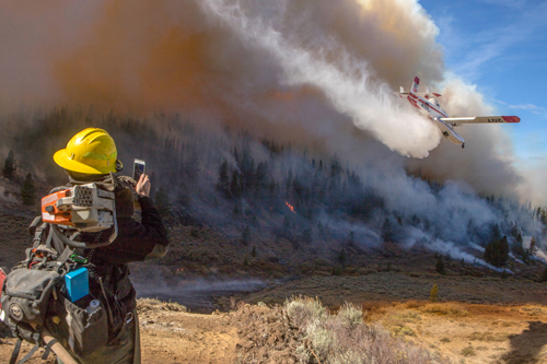 A wildland firefighter watches and takes picture with cell phone of a single engine airtanker dropping water over landscape of smoke and flames.