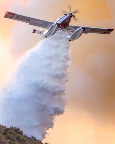 A single engine airtanker seen from directly above dropping a load of water over a hill.