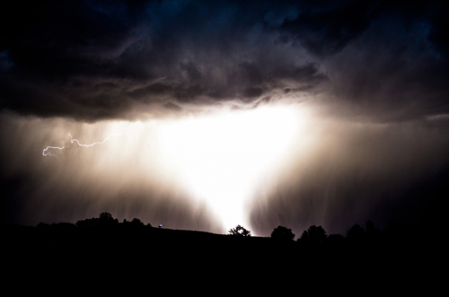 . Decorative. A large bolt of lightning lights up the night sky.