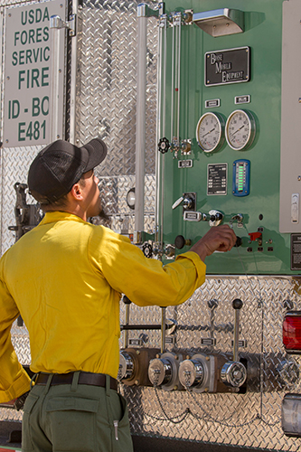 Photo of firefighter looking at dials at the back of a truck. Decorative