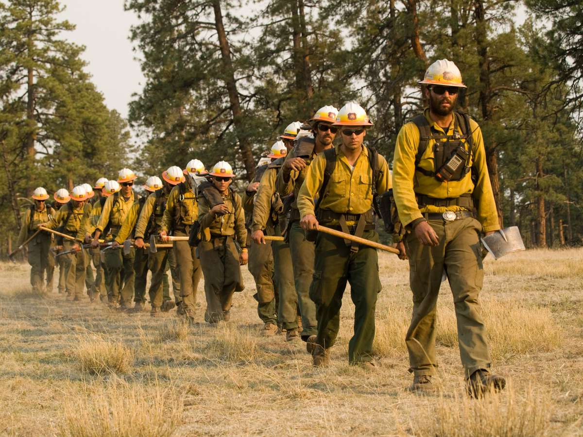 Photo of firefighters walking single file carrying tools and packs.