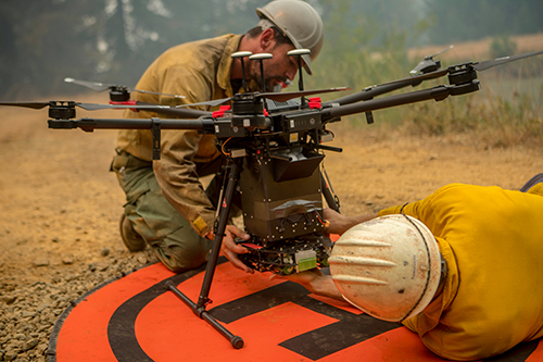 Photo of firefighter and drone. Decorative.