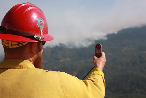 Photo of A wildland firefighter holds a weather meter out in front of him taking readings of the terrain. Decorative.