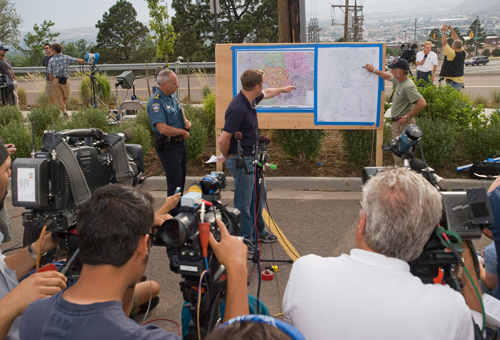 Two people pointing at large maps on a board outdoors, while news crews record the briefing. . Decorative