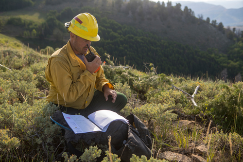 Photo of A wildland firefighter crouches on a mountain ridge while talking into a hand radio. Decorative.