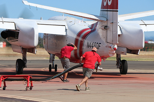 Two ground crew technicians walk toward back of aircraft dragging refueling hose.