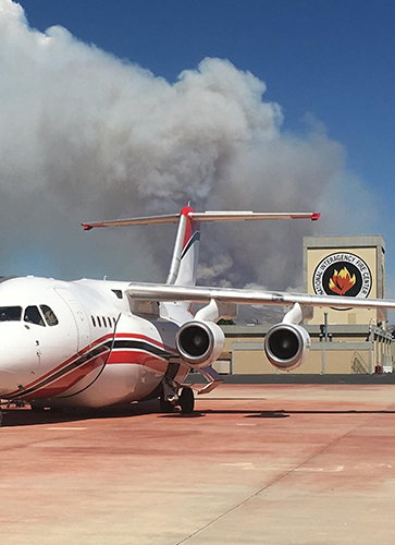 An airtanker sits on tarmac at the National Interagency Fire Center while large fire billows smoke in mountains beyond. Decorative.