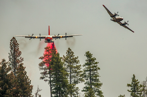 A single engine airtanker escorts an airtanker during a retardant drop.