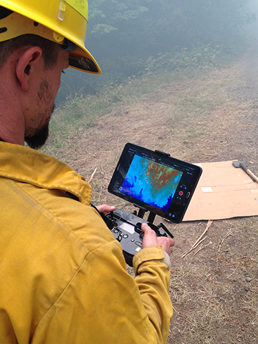 Two UAS specialist monitoring data on computer screens in a command post. Decorative