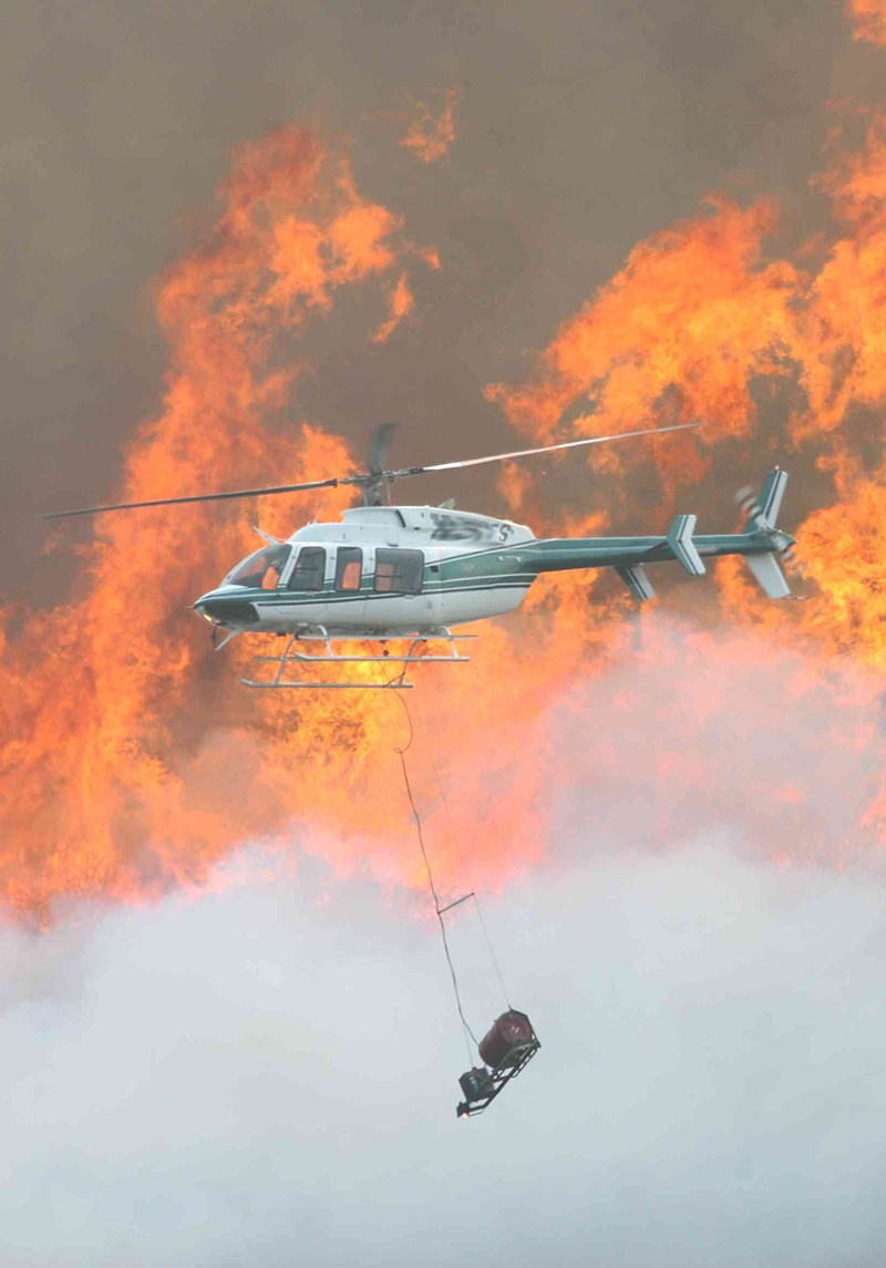 photo of helicopter with flames in the background