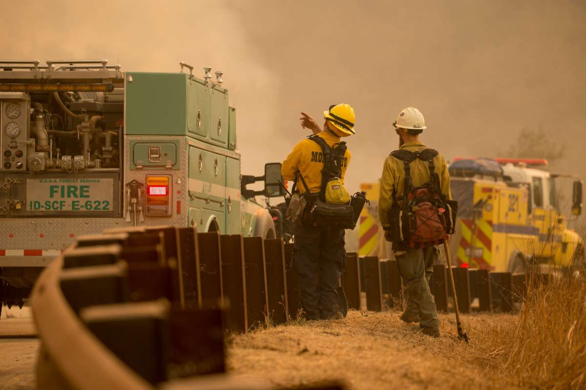 Photo of 2 firefighters on a smoky road with mobile equipment.
