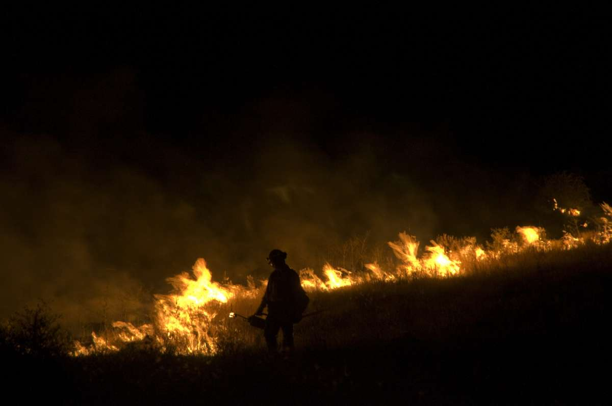photo of firefighter at night with burning fireline