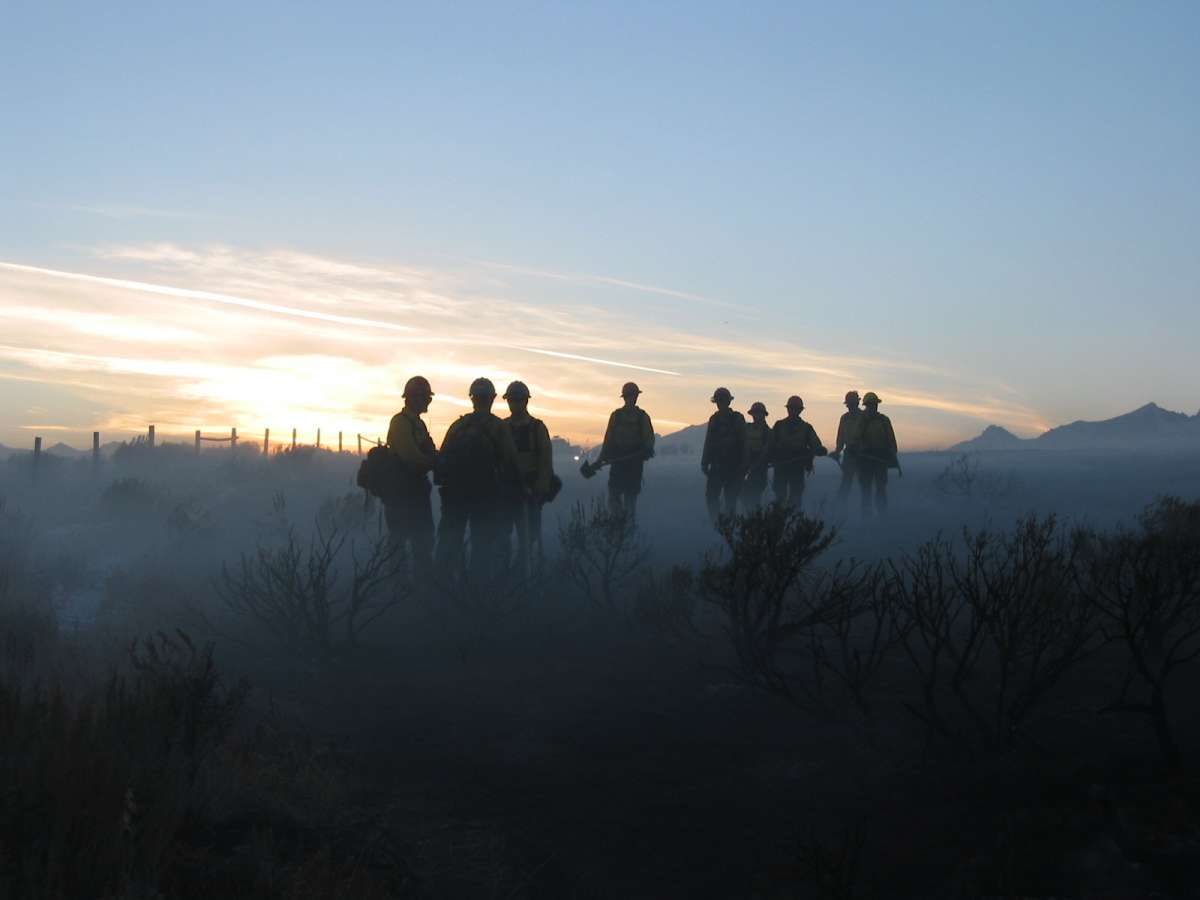 photo of several firefighters on a hill at sunrise