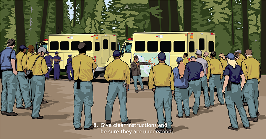 8. Give clear instructions and be sure they are understood. About 20 firefighters stand in a semi-circle in front of two crew buggies where a map has been put up. A supervisory firefighter points at the map and speaks to the group.