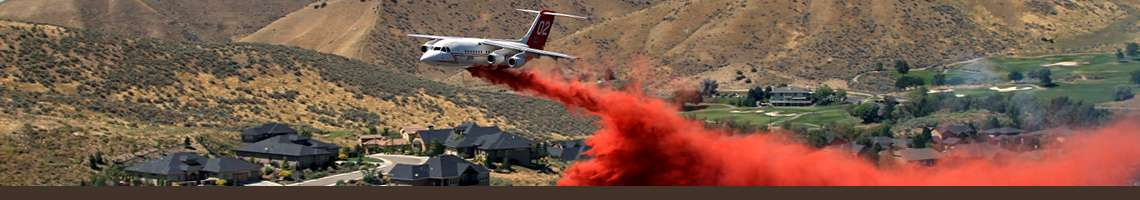 Decorative banner. A large airtanker dropping retardant over a neighborhood..