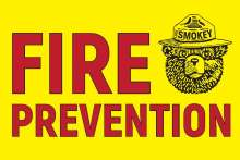 Fire prevention in red letters on bright yellow background with Smokey Bear