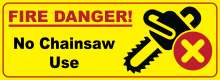 "Bright yellow background with red border; ""Fire Danger"" text; chainsaw icon with red X in circle; ""No chainsaw use"" text"