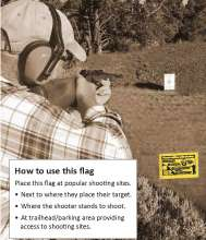 Man shooting with flag in ground next to him
