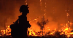 Silhouette of fire fighter standing in front of burning timber.