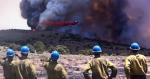 Photo of firefighters watching an airtanker drop retardant on fire.