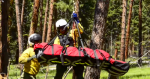 Image of firefighters loading an individual onto the end of a tether for a short-haul evac.