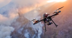 Image of a drone flying in the sky above smoke filled mountains.